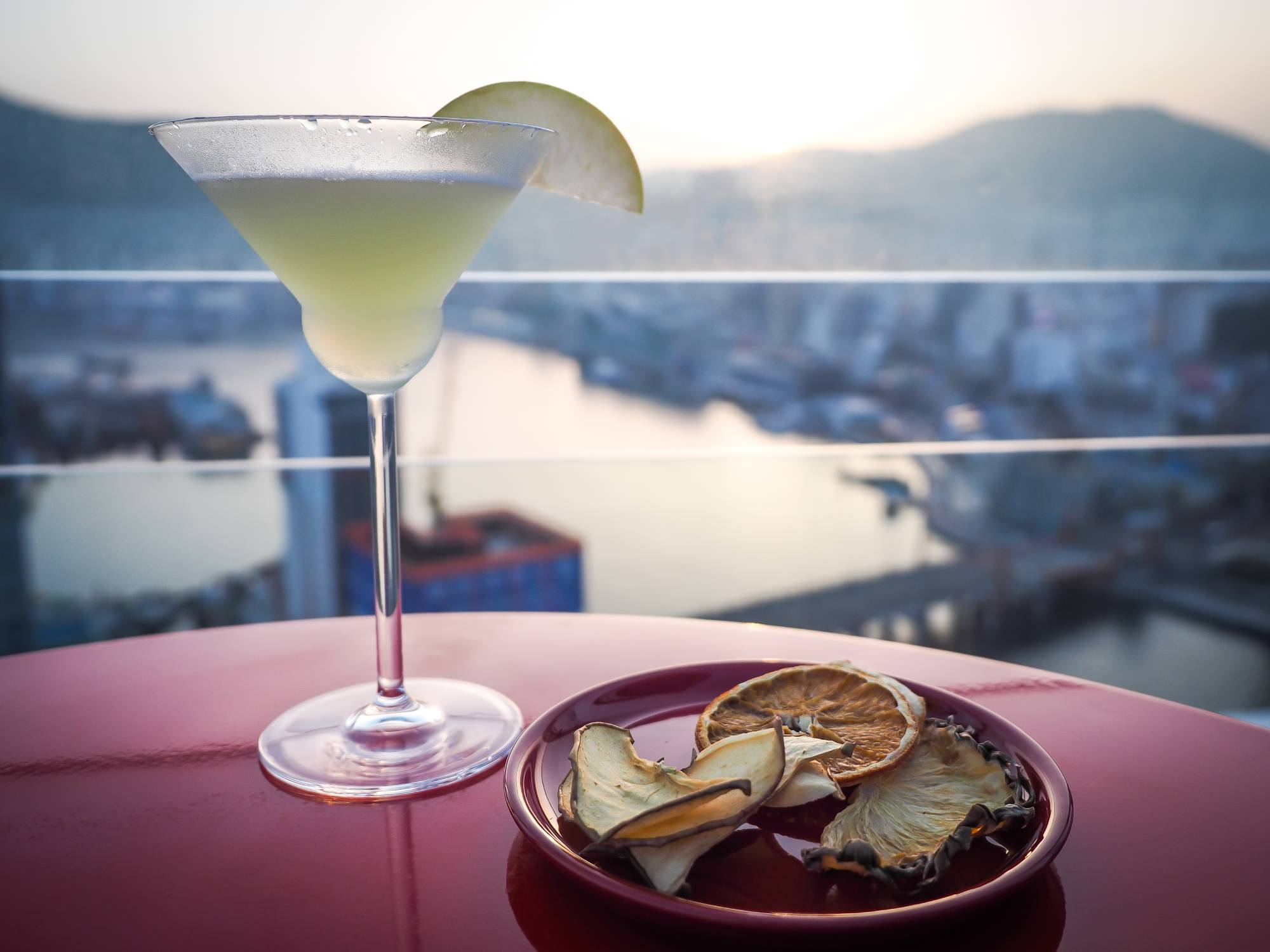 Apple martini with a view of the sun setting over Busan